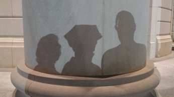 Shadow of Tanya Mikulas wearing 6-pointed PhD graduation tam with family on Shelby Hall pillar.